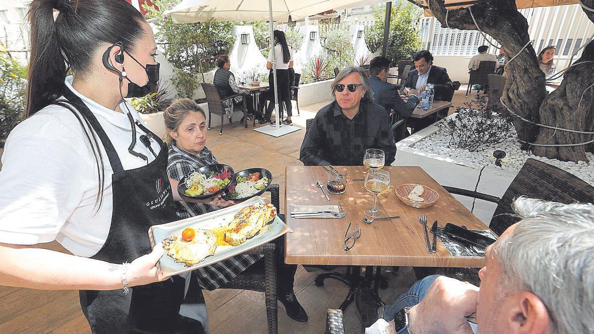 Una camarera sirve unas mesas en La Taberna Machete, en Castelló.
