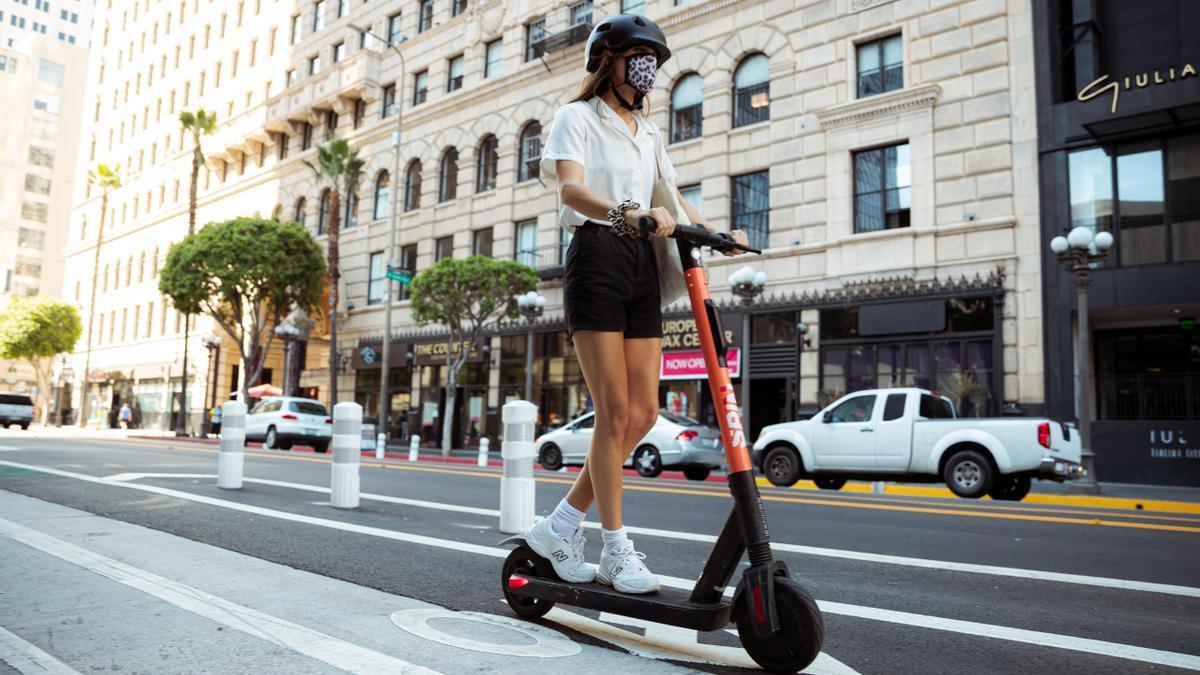 Una joven circula con un patinete por una ciudad.