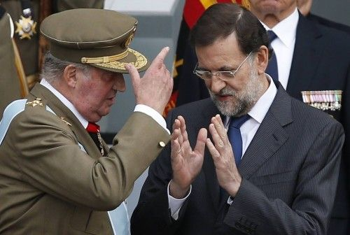 Spanish King Juan Carlos and Prime Minister Mariano Rajoy talk after a military parade marking Spain's National Day in Madrid