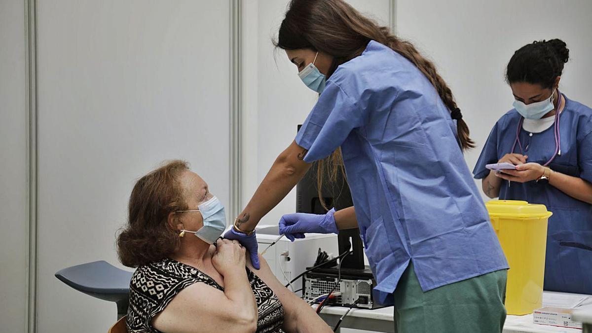 Una mujer recibe una dosis de la vacuna en el Polideportivo Germans Escalas.