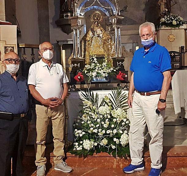 Vicente y Ceferino Cuadra, junto a Fernando Naredo, con la Virgen. A la derecha, Ernesto Seijas y Carmina Alonso, con su nieta Rita.   V. A.
