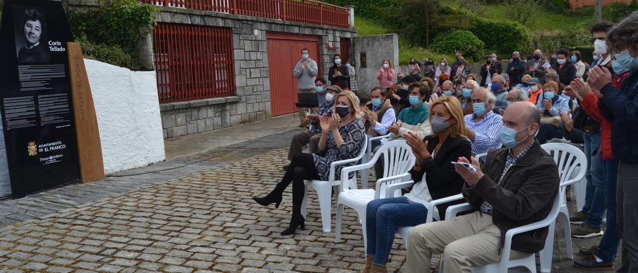 Por la derecha, sentados en primera fila, el director de Cultura, Pablo León; Begoña Tellado, hija de la escritora; y la edil Victoria Zarcero, en el homenaje, ante el panel. | A. M. S