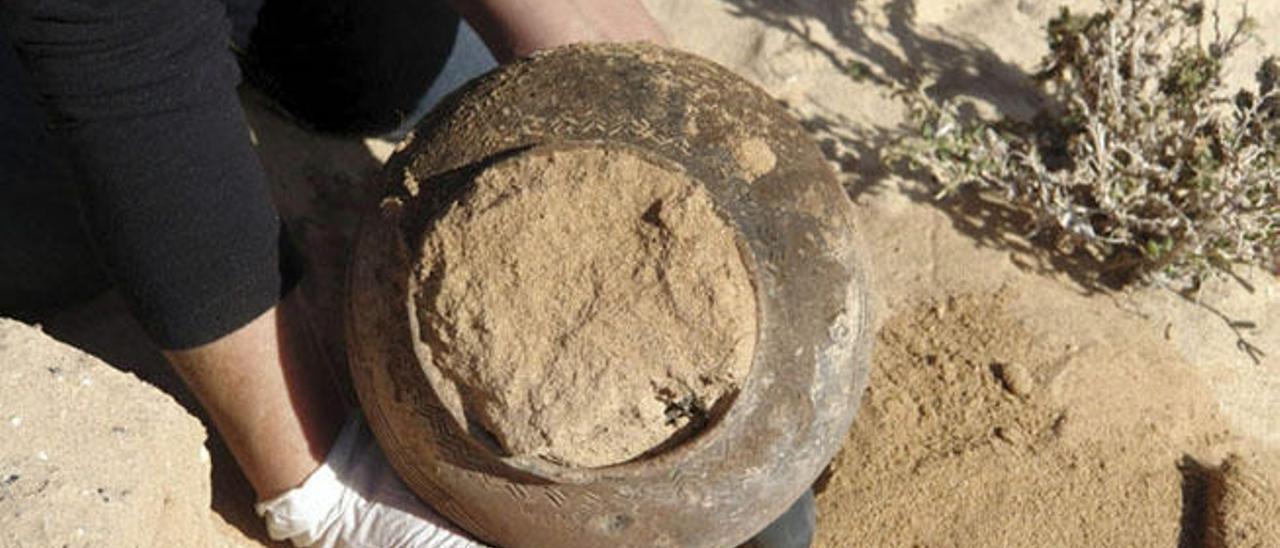 Momento en que una arqueóloga rescata una de las vasijas.