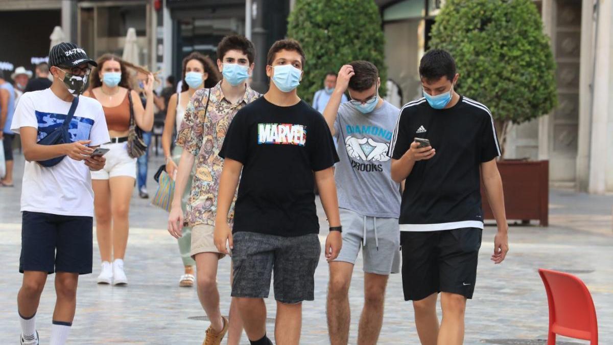 Jóvenes con mascarilla caminan por la calle.