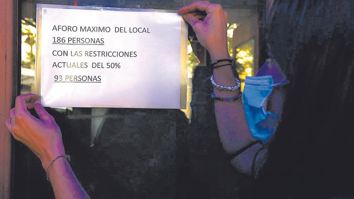 Un local de Zaragoza cuelga un cartel con sus aforos, una restricción que Badiola cree que ha funcionado.