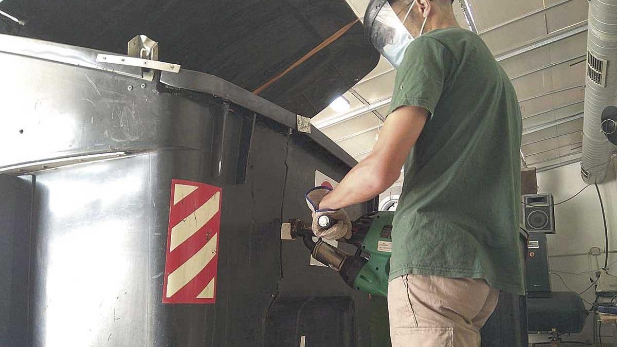 Un trabajador de la entidad social Mater Misericordiae repara un contenedor de basura.