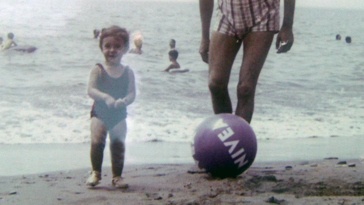 Una  niña juega en una playa de Málaga a finales de los 60 con una pelota de Nivea.