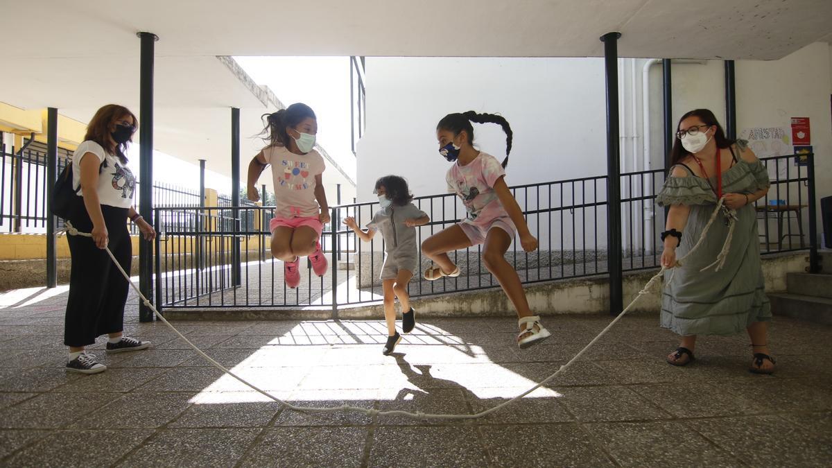 En el patio del CEIP Federico García Lorca unas niñas saltan a la comba ayudadas por dos monitoras.