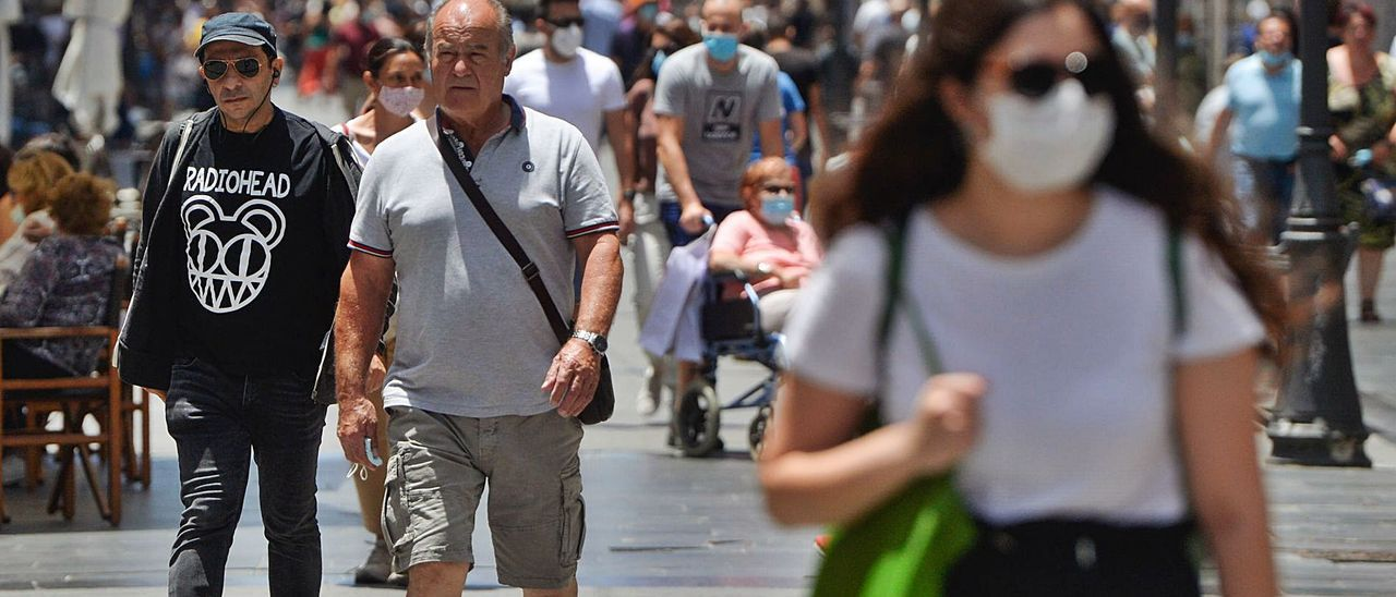 Grupos de personas que pasean, con y sin mascarilla, por la calle Triana de la capital grancanaria.     JOSÉ CARLOS GUERRA
