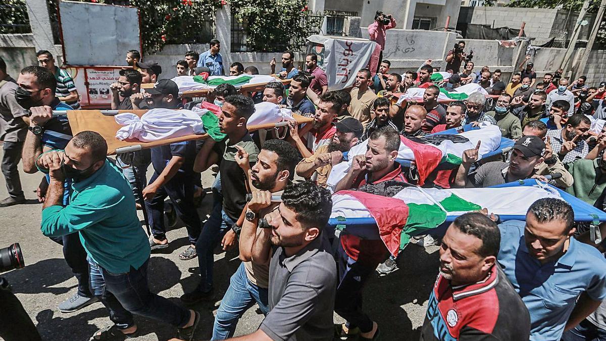 Desenes de persones porten els cadàvers dels deu morts d'una mateixa família a Shati.   EUROPA PRESS