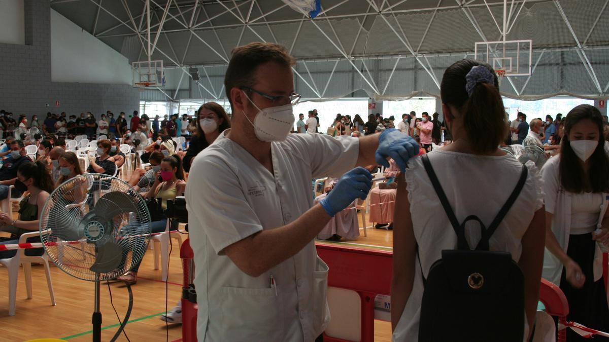 Un enfermero vacuna a una joven