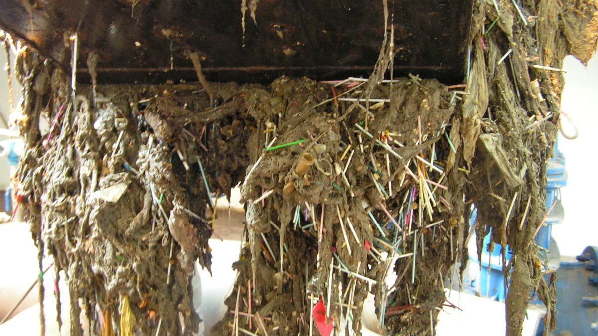 Imagen de archivo de una pala recogiendo basura despositada en la red de saneamiento