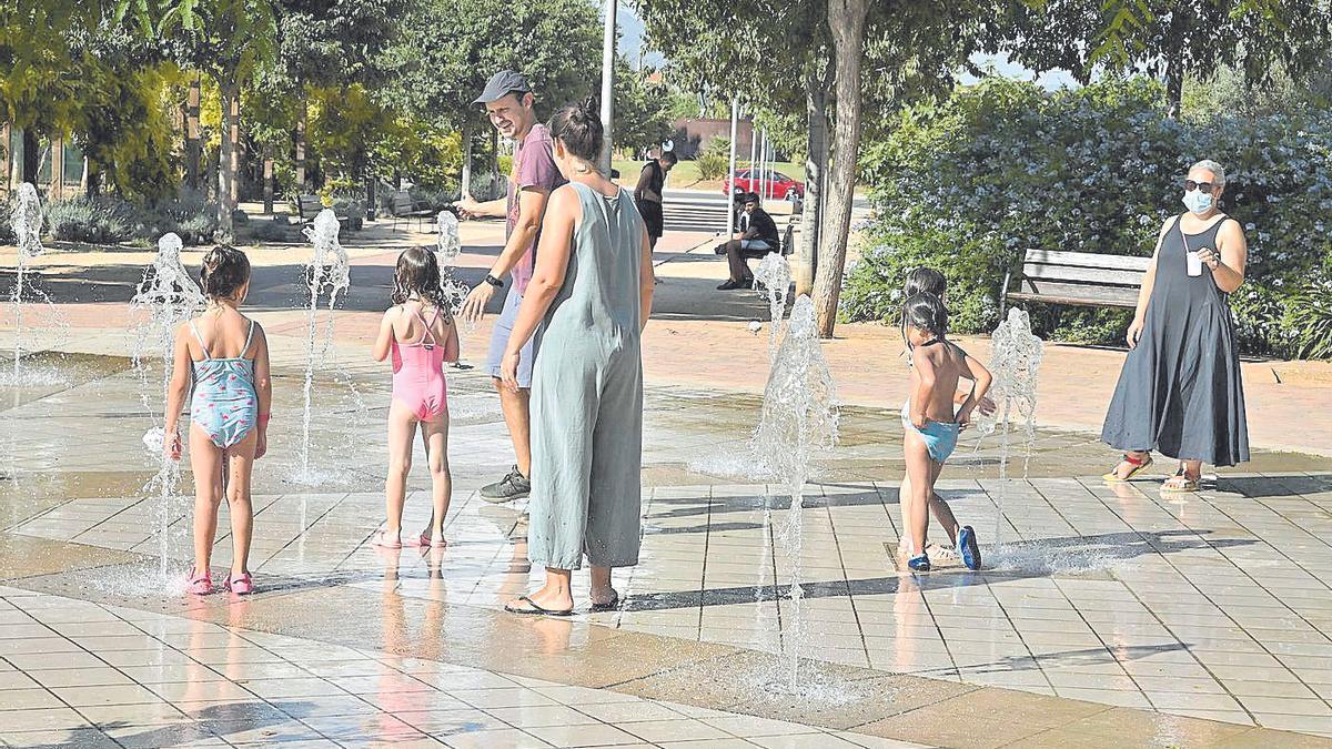 Unos niños se refrescan en la fuente del parque del Pont de Ferro de Castelló ante el sofocante calor.