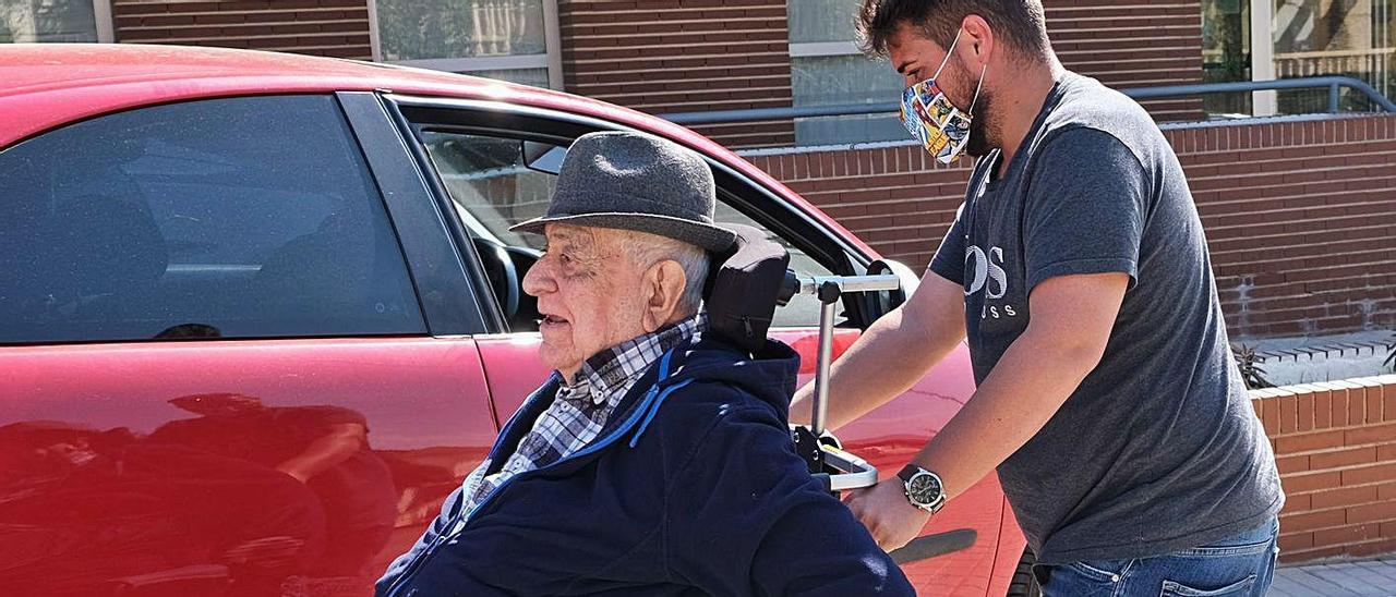 Un residente de La Molineta de Petrer, con su nieto, camino de casa para comer con la familia.