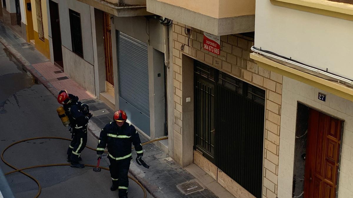 Dos bomberos acceden al inmueble donde la nevera ha causado un fuego.