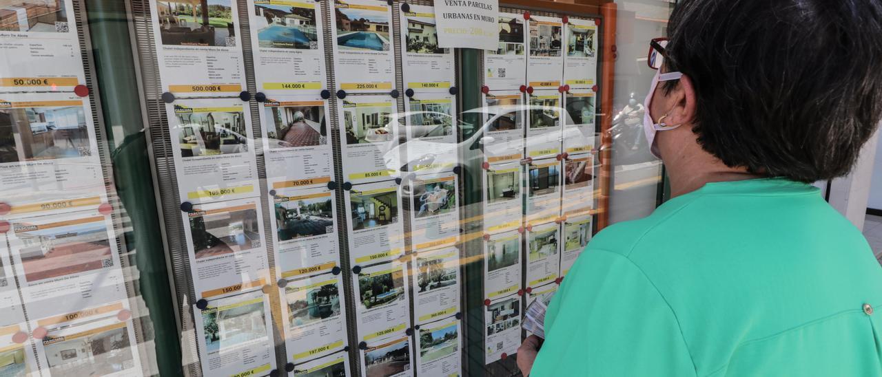 Una mujer mira el escaparate de una inmobiliaria.