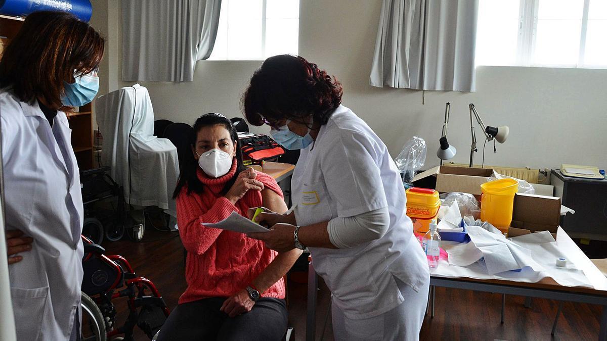 Una sanitaria del turno de tarde de Moaña, al mediodía de ayer mientras la enfermera Marina Fontán le administra la vacuna.   | // G. NÚÑEZ