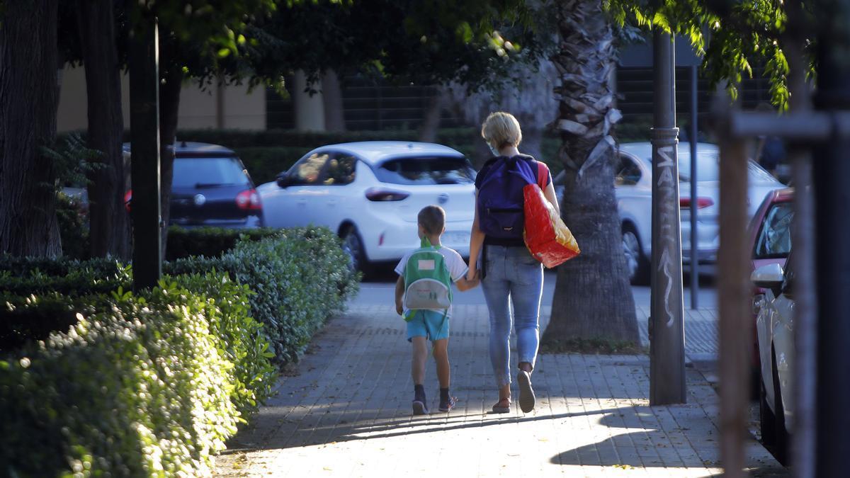 Una madre acompaña a su hijo al colegio.