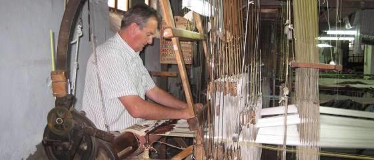 Un trabajador muestra cómo funcionan los telares históricos.