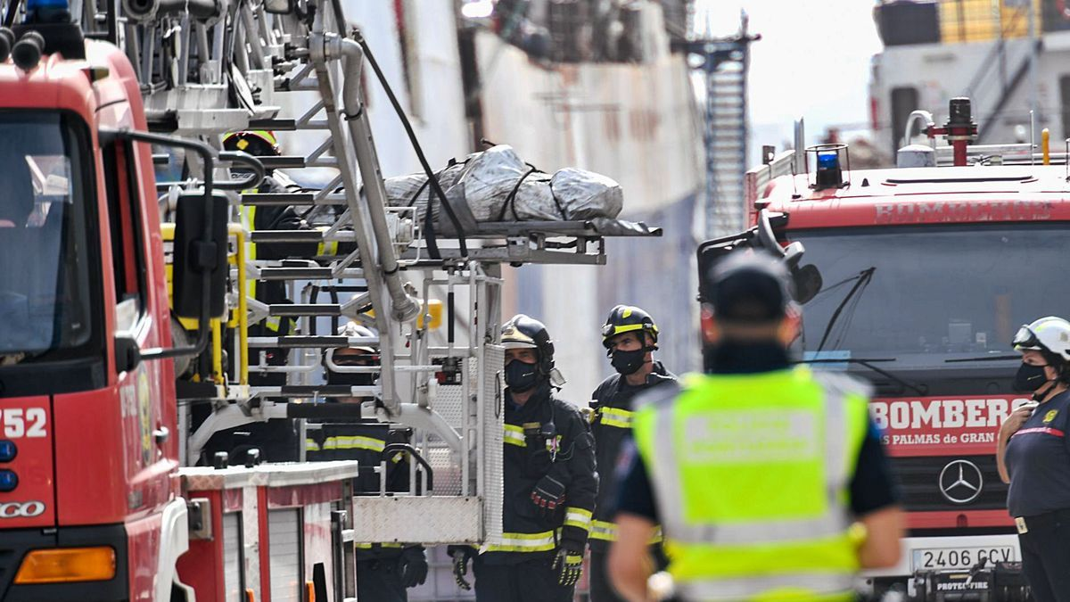 Los bomberos sacan del barco el primero de los tres cadáveres, a mediodía de ayer.