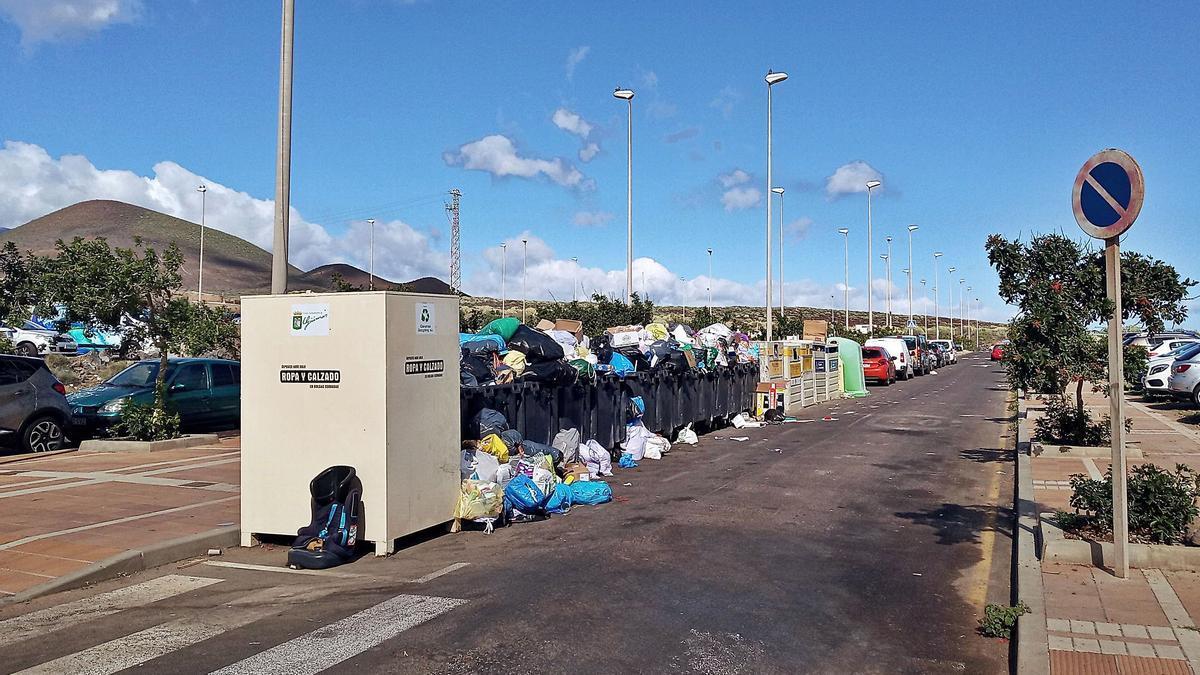 Los contenedores repletos de basura en el plan parcial El Puertito (i), las mesas de terrazas excediendo su espacio en Las Indias (arriba) y la arena invadiendo aparcamientos (sobre estas líneas).  | | E.D.