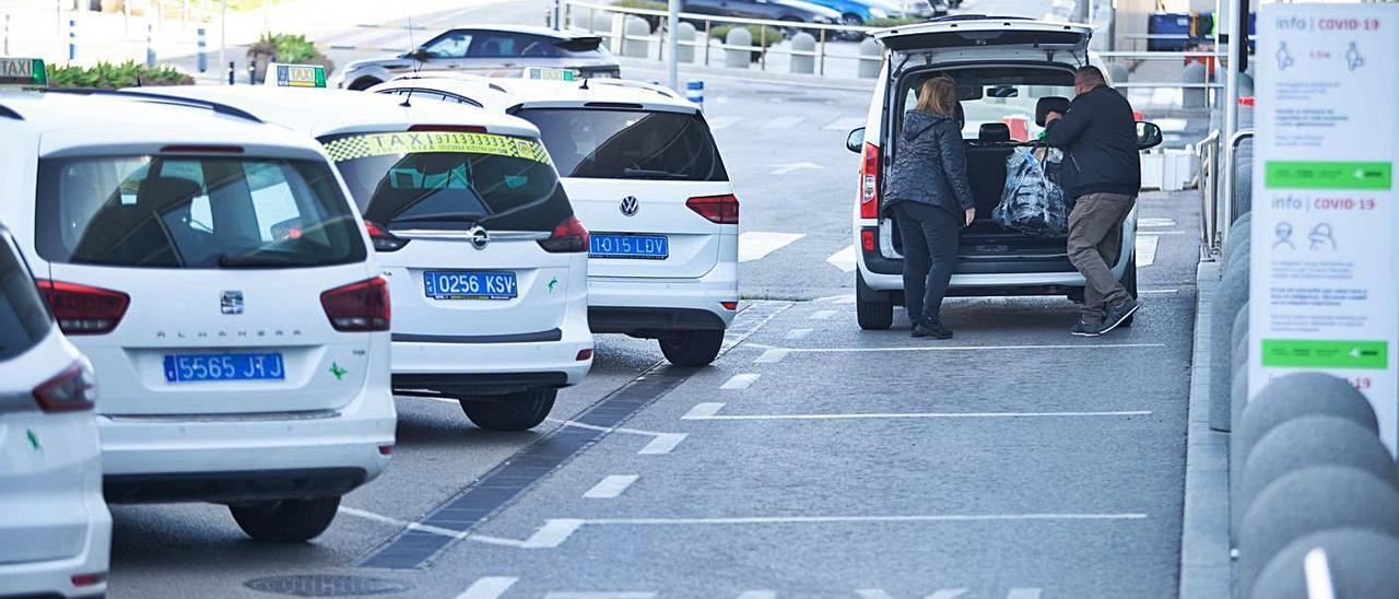 Varios taxis esperan su turno frente a la terminal del aeropuerto.