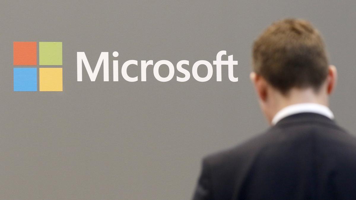 Un hombre frente al logo de Microsoft