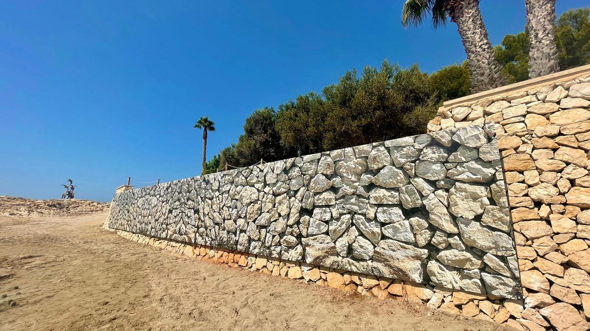 La lona colocada en el tramo derruido del muro de la playa de l'Ampolla
