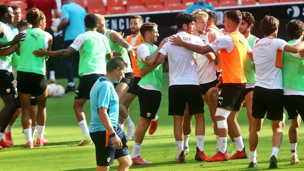 Los futbolistas del Valencia CF se divierten con un ejercicio durante el entrenamiento de ayer en el estadio de Mestalla.  | J.M. LÓPEZ