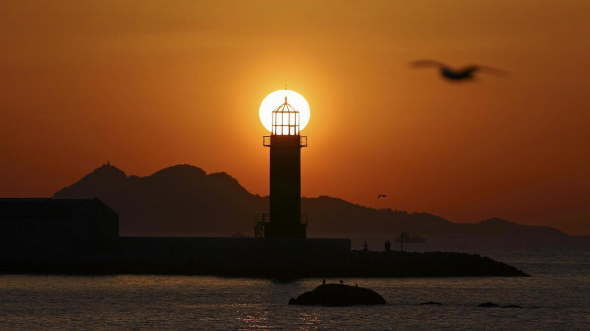 Una puesta de sol hoy en Bouzas sobre el faro del Museo del Mar y con las Illas Cíes de fondo. // FdV