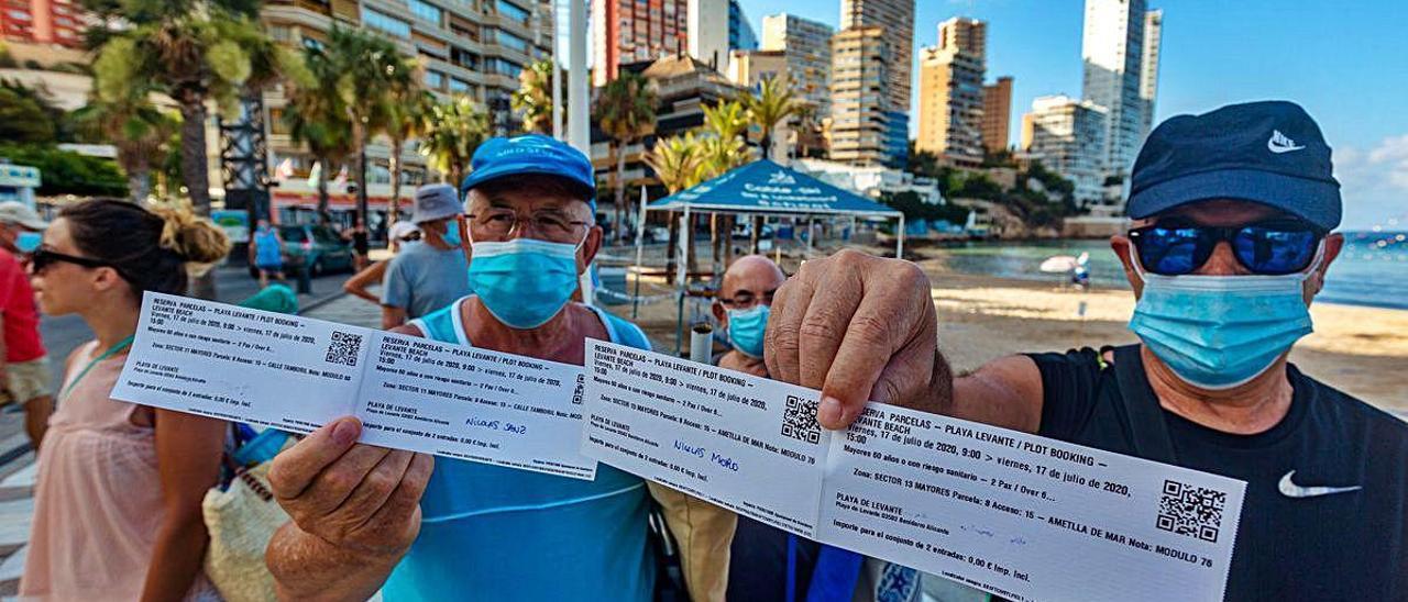 Dos bañistas muestran sus «entradas» para acceder a la playa de Levante.
