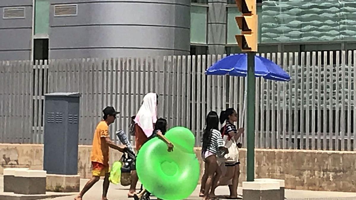 Una familia regresa de la playa con la sombrilla abierta y toallas en la cabeza. | RAÚL SANZ