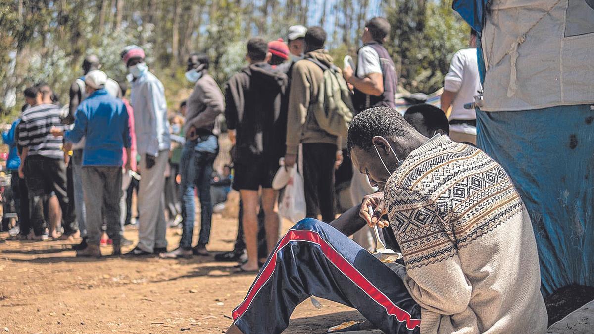 Colas para hacerse con comida de migrantes en el exterior de Las Raíces