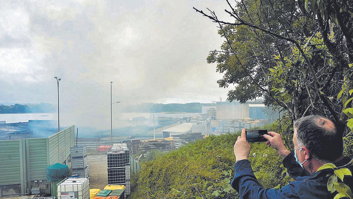 Un vecino de O Bodión (Boiro) graba un vídeo sobre el estado en el que quedó la nave de Jealsa tras el incendio del sábado. |  // IÑAKI ABELLA