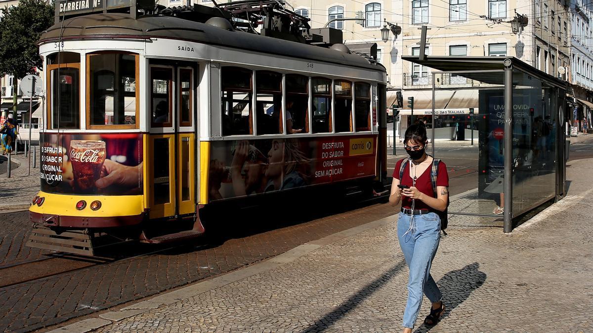 Una mujer con mascarilla camina frente a un tranvía en el centro de Lisboa