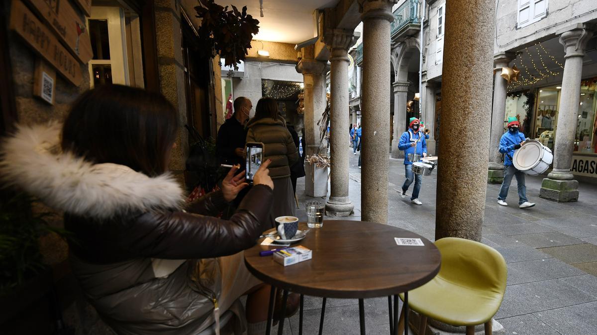 Una clienta en una terraza toma foto de la animación navideña callejera en Pontevedra.