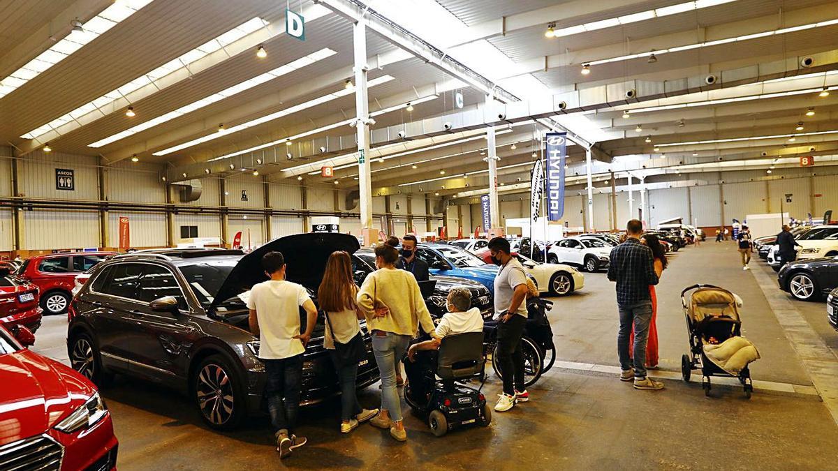 Un grupo de personas comprueba el estado de uno de los coches ofertados en la Feria de Zaragoza