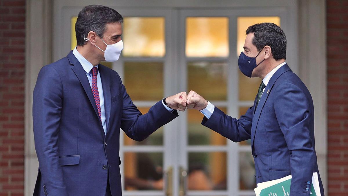 Pedro Sánchez y Juanma Moreno se saludan en la entrada de la Moncloa antes de la reunión ayer entre presidentes.