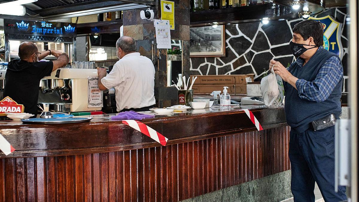 Un cliente pide comida para llevar en un bar de la capital tinerfeña.     CARSTEN W. LAURITSEN