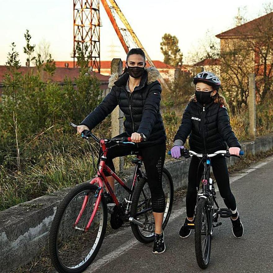Eva Meana y la pequeña Gabriela Pool, en sus bicicletas, junto a la mina de La Camocha. | |  JUAN PLAZA