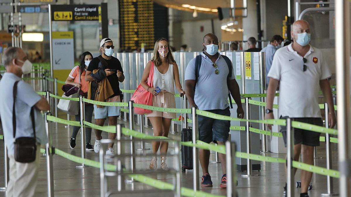 Un grupo de turistas se dispone a pasar el control previo al embarque en el aeropuerto de Manises durante el pasado verano.   DANIEL TORTAJADA
