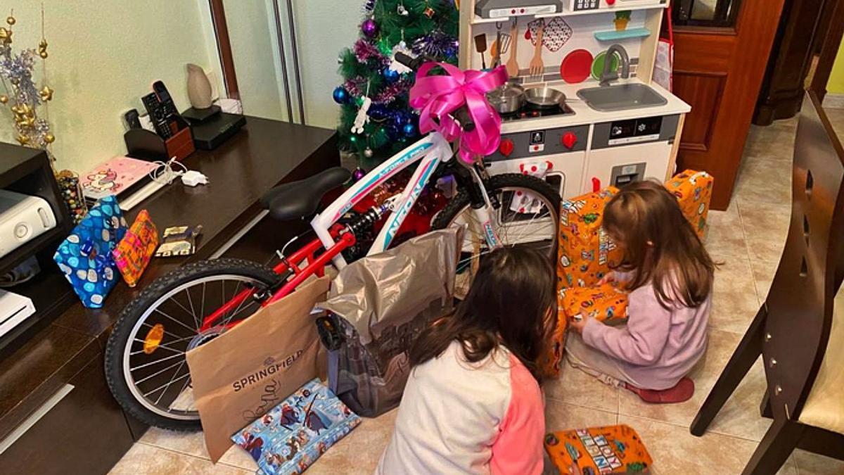 Dos niñas abriendo sus regalos de Reyes.   E. P.