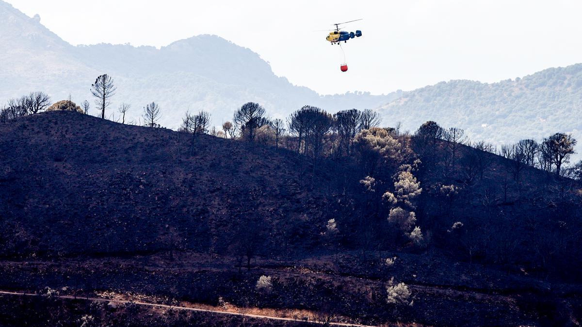 Un helicóptero contra incendios en la zonas quemadas por el incendio de Sierra Bermeja