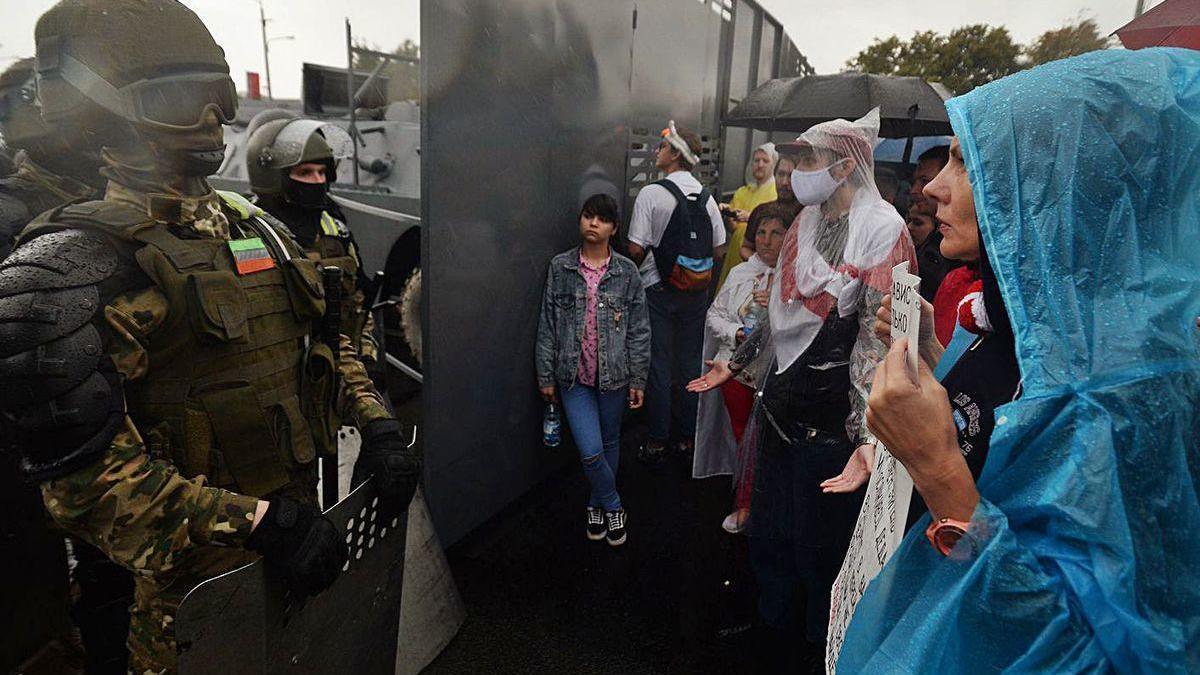 Una mujer, ayer, en Minsk, ante una barrera policial antidisturbios que impedía el paso a una nueva manifestación masiva.