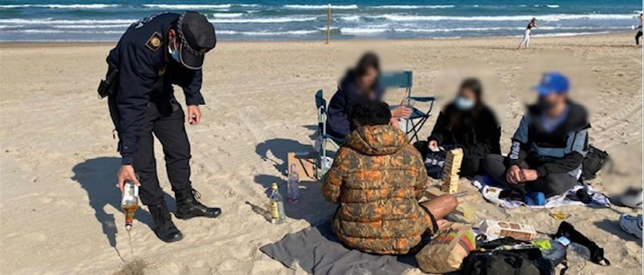 Un policía requisa y tira el alcohol a un grupo en la playa, este fin de semana en Alicante