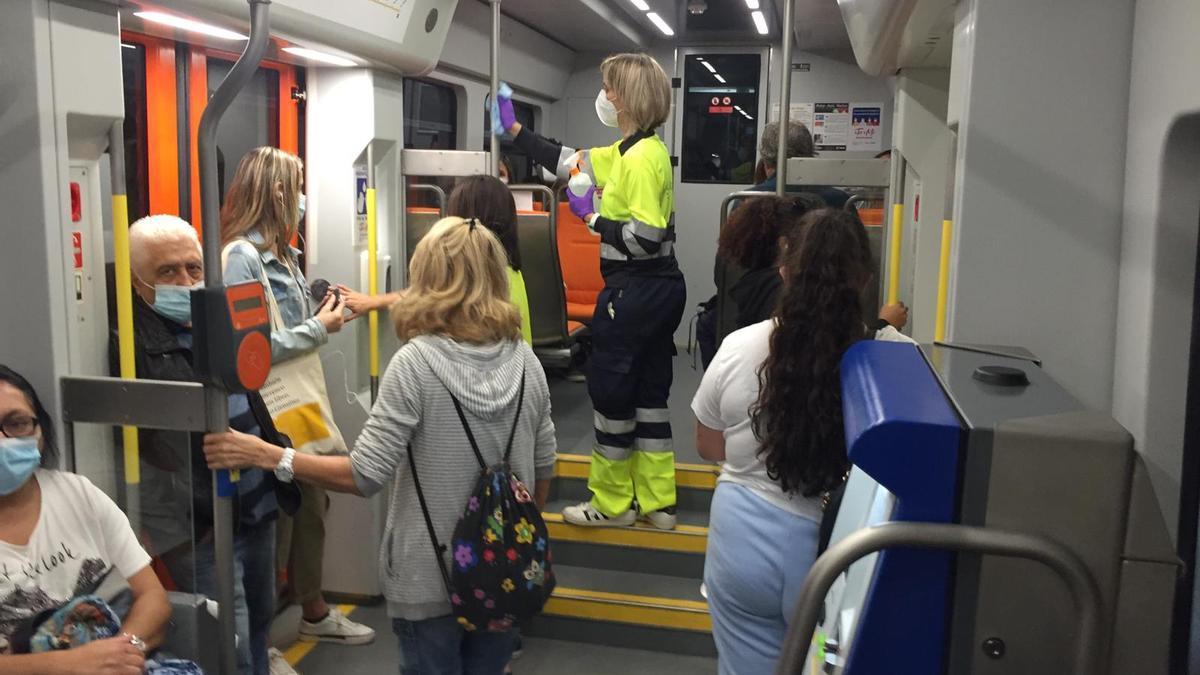 Una operaria limpia una unidad del tranvia en pleno recorrido
