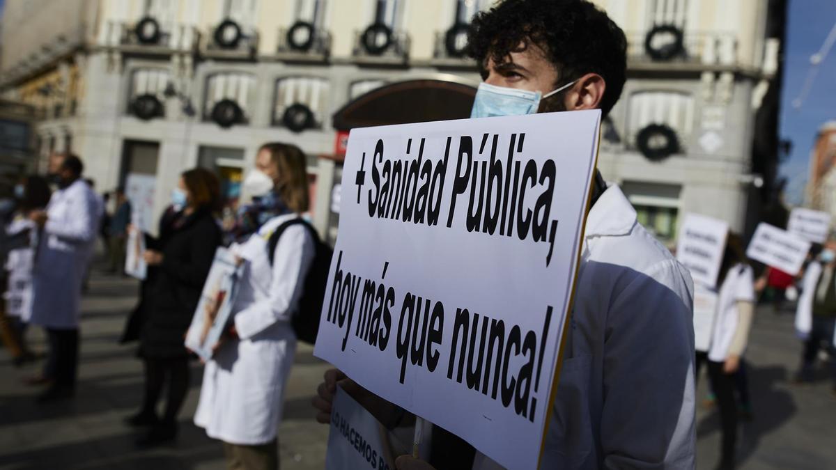 Un trabajador sanitario sostiene una pancarta durante una concentración.