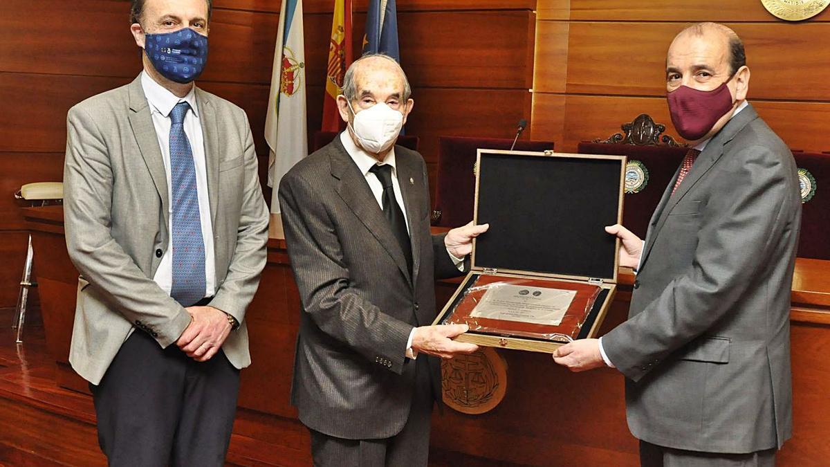 Liaño Flores, en el medio, recibe la placa de manos de Augusto Pérez Cepeda.  | // L. O.