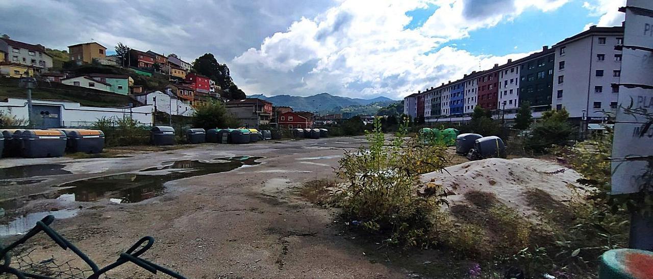 La parcela de Langreo Centro que se destinará a viviendas, con el barrio del Puente a la izquierda.   M. Á. G.