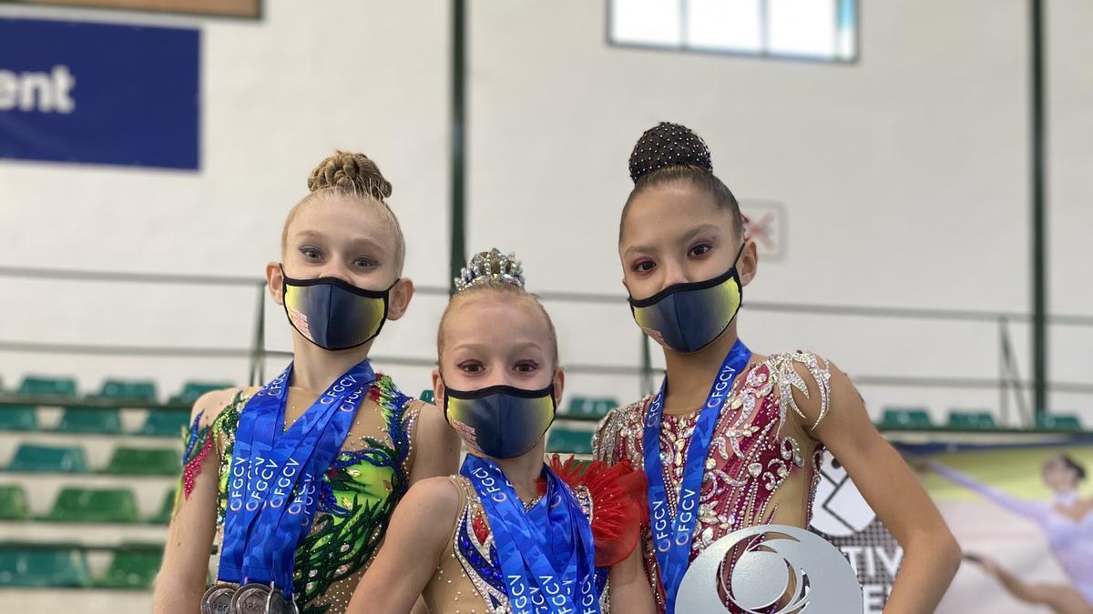 Las pequeñas gimnastas muestran sus trofeos